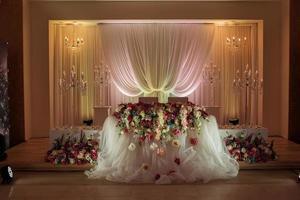 mesa festiva decorada com uma composição de flores brancas, vermelhas e rosa e folhagens no salão de banquetes