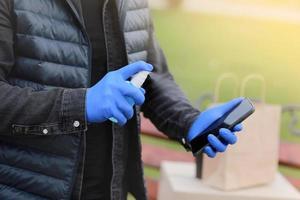 serviço de entrega de correio durante o coronavírus, pandemia de covid-19, correio com as mãos em luvas borrifando álcool desinfetante spray em um telefone celular perto de caixas de papelão ao ar livre