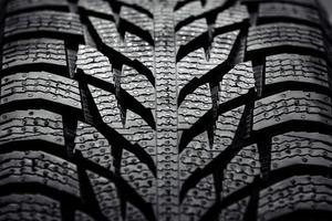 close-up de um pneu de carro novo, plano de fundo texturizado foto