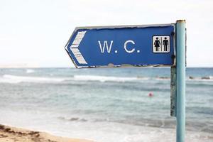 direção ao banheiro em uma praia. inscrição wc na placa de banheiro pendurada em um poste com um fundo do mar e do céu foto