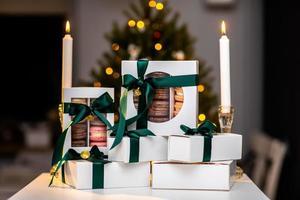 macaroons franceses em caixas brancas com fita verde. árvore de natal com bokeh e velas no fundo. cozinha francesa europeia moderna. tema de natal, cartão de feliz natal. clima de ano novo. foto