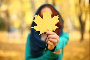 garota segurando uma folha de bordo amarela no outono. folhas de outono. foco seletivo.