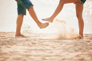 jovem casal brincando com areia. estilo de vida de verão. pés na areia na praia