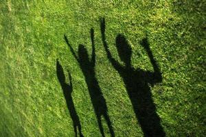silhueta de três pessoas em pé com as mãos estendidas na grama verde foto