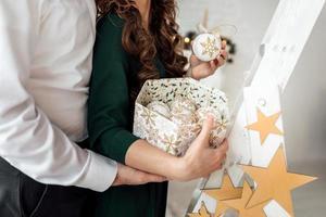 decorar a árvore de natal. esposa e marido segurando uma caixa com brinquedos de Natal em estilo escandinavo. foto de close-up das mãos.