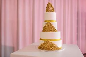 bolo de casamento com ouro. bolo de casamento na mesa branca. 3 camadas cobertas com fondant de marfim pulverizado com spray de pérolas e rosas amarelas feitas de pasta de açúcar.
