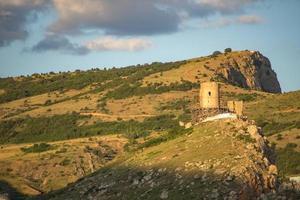 vista da fortaleza genovesa na encosta de uma montanha com um céu azul nublado na Crimeia foto