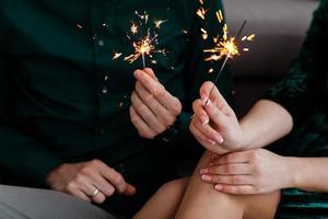 mãos masculinas e femininas segurando luzes acesas de bengala. linda jovem família feliz comemorando o Natal juntos. casal segurando luzes de bengala.
