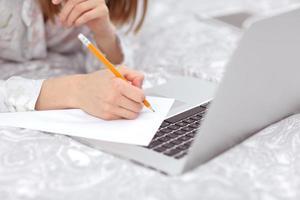 close-up da mão de uma mulher usando um lápis para escrever. garota trabalhando, aprendendo e usando o computador laptop no quarto. trabalhador autonomo. escrever, digitar. comunicação e tecnologia, conceito de auto-estudo.