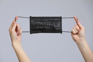 as mãos de uma mulher segurando uma máscara médica facial em fundo cinza, close-up, espaço de cópia, epidemia de gripe, temporada de alergias, proteção contra vírus - covid-19 e coronavírus. foto