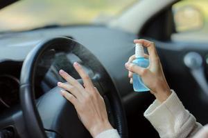 mão de uma mulher borrifando álcool, spray desinfetante no carro, segurança, prevenir a infecção do vírus covid 19, coronavírus, contaminação de germes ou bactérias. desinfetante de álcool, conceito de higiene