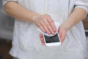 mulher desinfetando o telefone com lenço umedecido anti-séptico. guardanapo anti-séptico para prevenir a propagação de germes, bactérias e coronavírus. prevenção contra coronavírus. prevenir a doença coronavírus após um local público. foto
