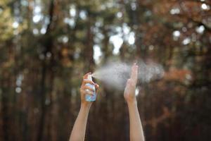 mãos de mulheres aplicando álcool em spray ou anti-bactérias em spray ao ar livre para evitar a propagação de germes, bactérias e vírus, tempo de quarentena, foco em fechar as mãos. coronavírus. copie o espaço.