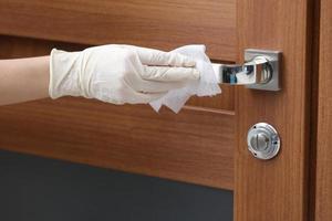 pessoa desinfeta e limpa a maçaneta da porta com lenços umedecidos antibacterianos para proteger contra vírus, germes e bactérias durante o surto de coronavírus e epidemia de cobiça. casa limpa.