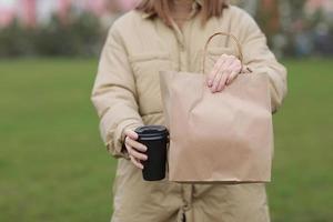 xícara para viagem com café, simulação de marca de identidade. close-up de saco de papel e copo de papel na mão feminina. jovem carrega sacolas de compras e café foto