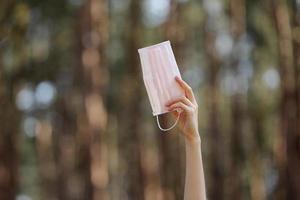 máscara protetora médica na mão da menina isolada no fundo da natureza. proteção de máscara facial contra infecção de vírus. coronavírus - 2019. conceito de cuidados de saúde. foco seletivo.
