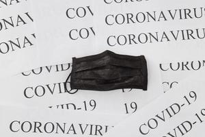 máscara médica preta em fundo de inscrições de coronavírus e covid-19. conceito de proteção contra poluição, vírus e gripe. equipamento cirúrgico profissional foto