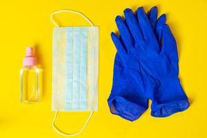 luvas de látex, máscara médica e anti-séptico em fundo amarelo foto