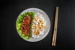 frango teriyaki com arroz branco no prato foto