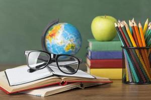 mesa do aluno com lápis de cor, livro aberto e óculos
