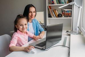mãe e filha posando com laptop foto