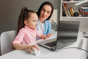 mãe ajudando filha com educação virtual foto