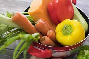 feche legumes frescos para a sopa na panela vermelha foto