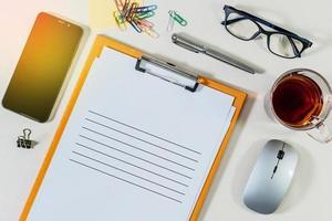 Prancheta de pasta de arquivos de escritório com papel branco para inscrição e material de escritório na mesa