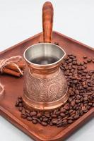 cafeteira de cobre ou ibrik com grãos de café e paus de canela. em uma placa de placa de madeira. fundo branco foto