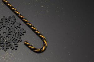 bastão de doces preto e dourado em fundo preto foto