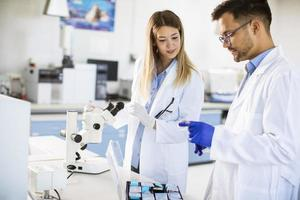 grupo de jovens pesquisadores analisando dados químicos em laboratório foto