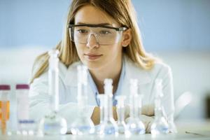 pesquisadora médica ou científica olhando para frascos com soluções em um laboratório foto