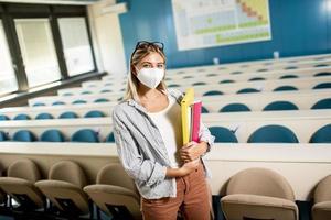 aluna usando máscara médica protetora facial para proteção contra vírus em pé na sala de aula foto