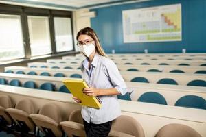 aluna usando máscara médica protetora facial para proteção contra vírus em pé na sala de aula