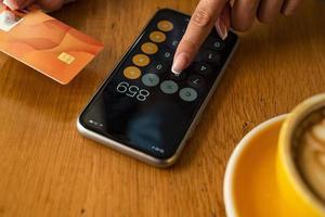mulher pagando e fazendo compras usando cartão de crédito e calculadora móvel para smartphone foto