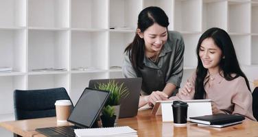 dois colegas de trabalho sorrindo enquanto usam um tablet