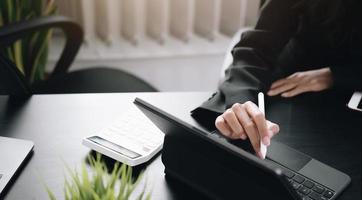 close-up de uma pessoa usando uma caneta em um computador tablet
