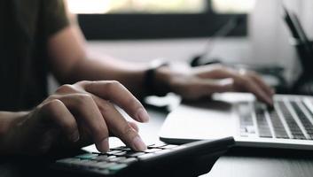 close-up de mãos em uma calculadora e laptop