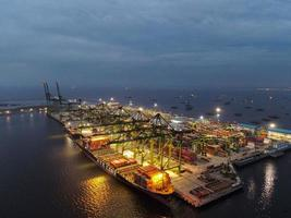 Jacarta, Indonésia 2021- vista aérea de carregamento e descarregamento de navio de contêiner em porto de alto mar, importação logística e transporte de frete de exportação por navio de contêiner em mar aberto à noite