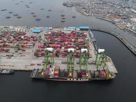 Jacarta, Indonésia 2021- vista aérea do carregamento e descarregamento de um navio de contêiner em um porto de alto mar, transporte de carga de importação e exportação