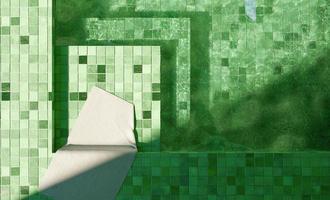 vista superior da piscina de azulejos verdes com uma toalha branca, renderização em 3D foto
