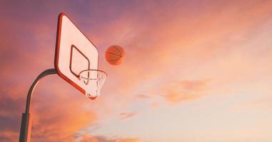 cesta de basquete sobre um pôr do sol quente com nuvens e a bola caindo na cesta, renderização em 3D