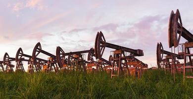paisagem com bombas de óleo enferrujadas e abandonadas e grama crescendo ao redor com o pôr do sol, renderização em 3D foto