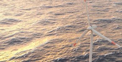 paisagem com turbina eólica em um mar agitado com pôr do sol quente, renderização 3D