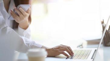 pessoa usando um telefone enquanto digita em um laptop foto