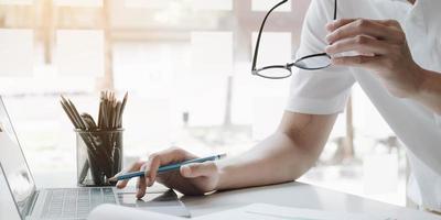 profissional segurando óculos e trabalhando em um laptop