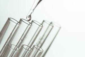 close-up de líquido sendo jogado em tubos de ensaio foto