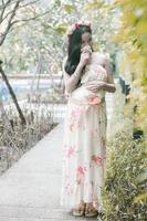 mulheres grávidas cheirando flores