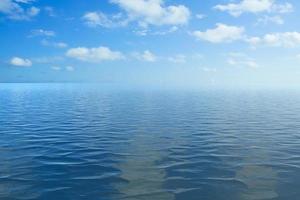 vista do mar com céu azul nublado ao pôr do sol foto