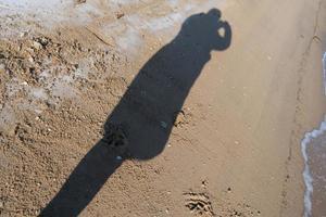 silhueta de uma pessoa tirando uma foto na praia